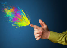 Colorful splashes are coming out of gun shaped hands Royalty Free Stock Images