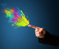 Colorful splashes are coming out of gun shaped hands. Colored splashes are coming out of gun shaped hands royalty free stock image