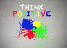 Colorful splashes and think positive writing, words banner Royalty Free Stock Images