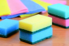 Colorful sponge and rags for cleaning ware and house cleaning. Cleaning sponge with scrub and rags set on a wooden table. Closeup. Cleaning sponge. Cleaning Royalty Free Stock Photos