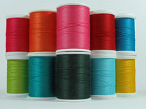 Colorful spools of cotton thread. Red, pink, orange, yellow, green and blue spools of cotton thread used for sewing Royalty Free Stock Image