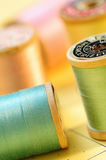 Colorful spools of pastel colored thread. With focus on foreground spools stock photos