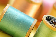 Colorful spools of pastel colored thread. With focus on foreground spools stock photography