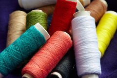Colorful spools of thread pile Stock Photos