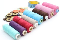 Colorful spools of thread, tape measure and buttons Royalty Free Stock Photo
