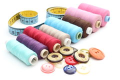 Colorful spools of thread, tape measure and buttons. Colorful spools of thread with a tape measure and buttons Royalty Free Stock Photos
