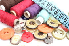Colorful spools of thread, tape measure, thimble and buttons Stock Photos