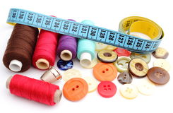 Colorful spools of thread, tape measure, thimble and buttons. Colorful spools of thread with a tape measure, thimble and buttons isolated on white Royalty Free Stock Photography