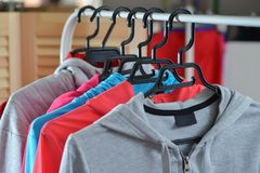 Colorful sport shirts and jackets hanging on clothes rack at a fashion store.  Royalty Free Stock Photo