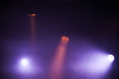 Colorful spot lights with strong beams. In dark fog, stage illumination background photo Stock Photography