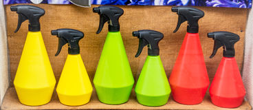 Colorful spray bottles in the window. Symbol of flowers maintenance, assortment, plastic products, traffic lights Stock Photos