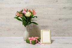 Colorful spring bouquet of rose, chrysanthemum and alstroemeria. Flowers in a vase with empty photoframe and gift box on wooden background royalty free stock photography