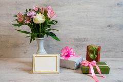 Colorful spring bouquet of rose, chrysanthemum and alstroemeria. Flowers in a vase with empty photoframe and gift boxes on wooden background royalty free stock photo