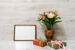 Colorful spring bouquet of rose, chrysanthemum and alstroemeria. Flowers in a vase with empty photoframe and gift boxes on wooden background stock images