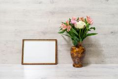 Colorful spring bouquet of rose, chrysanthemum and alstroemeria. Flowers in a vase with empty photoframe on wooden background royalty free stock images