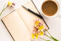 Colorful spring flowers, with blank open diary for text and cup of coffee. Colorful spring flowers, with blank open diary for text and cup of coffee, on white Royalty Free Stock Images