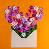 Colorful spring flowers in envelope, flower delivery and love concept Royalty Free Stock Photos