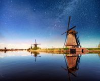 Colorful spring night with traditional Dutch windmills canal in Rotterdam. Wooden pier near the lake shore. Holland Royalty Free Stock Image