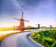 Colorful spring night with traditional Dutch windmills canal in Rotterdam. Wooden pier near the lake shore. Holland Stock Photos