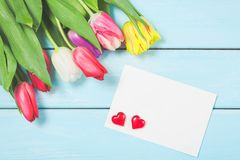 Colorful spring tulip flowers with blank photoframe and hearts on light blue wooden background as greeting card with free space. M. Othersday or spring concept royalty free stock photography