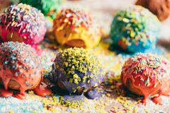 Sprinkled donuts laying on a messy counter. Colorful sprinkled donuts laying in rows on a messy kitchen counter. Delicious treats Royalty Free Stock Photo