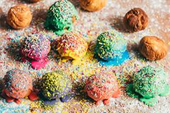 Colorful sprinkled doughnuts on a dirty counter. Couple of colorful sprinkled doughnuts laying in rows on a dirty kitchen counter Royalty Free Stock Image