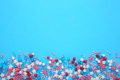 Colorful sprinkles on a blue background, top view with copy space. Colorful sprinkles on blue background, top view with copy space stock images