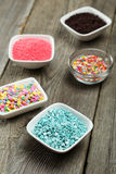 Colorful sprinkles in bow on grey wooden background Royalty Free Stock Photos