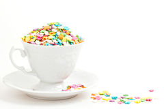 Colorful sprinkles in a cup on white Royalty Free Stock Images