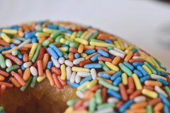Colorful sprinkles on donut close-up royalty free stock photo