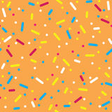 Colorful Sprinkles Donut Glaze Seamless Pattern. Donut glaze seamless pattern. Cream texture with topping of colorful sprinkles and beads on orange background Stock Photo