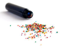 Colorful sprinkles spilled from a jar. On white table royalty free stock photo