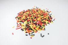 Colorful sprinkles spilled from a jar on white table Royalty Free Stock Photos