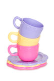 Colorful stack of toy cups and toy plates. A pile of three coloreful toy tea cups stacked on top of three toy plates Stock Images