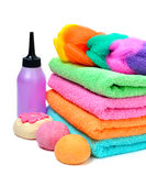 Colorful stacked spa towels, bath bombs and shampoo bottle isola Stock Image
