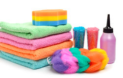 Colorful stacked spa towels, sea salt, mop and shampoo bottle is Stock Photos