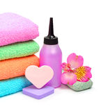 Colorful stacked spa towels, sponges and shampoo bottle Stock Images