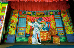 Colorful stage of chinese theater and one actor playing a role in a traditional dramatic play. LAMPANG, THAILAND - FEB 18: Colorful stage of chinese theater and Royalty Free Stock Image