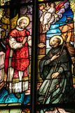 Colorful stain glass window in a church. Depicting two religious figures and an angel above in heaven Stock Photography