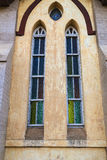Colorful stained glass in a church architectural detail. Vertical perspective of an architectural detail of colorful stained glass in a church wall royalty free stock photo