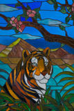 Colorful stained glass depicting a tiger. Colorful stained glass with a tiger behind palm leaves on Hawaii island Stock Image