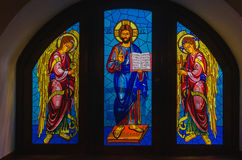 Colorful stained glass window with a picture of Jesus and the an. Gels. Window Panagia of Kykkos stock photography