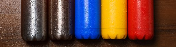 Colorful stainless thermo bottles, on a wooden table sprayed with water. Matte red bottle, blue, yellow and platinum color. With s. Unlight effect stock photos