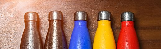 Colorful stainless thermo bottles, on a wooden table sprayed with water. Matte red bottle, blue, yellow and platinum color. With s. Unlight effect royalty free stock photos