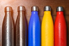 Colorful stainless thermo bottles, on a wooden table sprayed with water. Matte red bottle, blue, yellow and platinum color. With s. Unlight effect stock photography