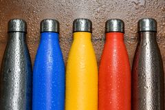 Colorful stainless thermos bottles on a wooden table sprayed with water. stock photos