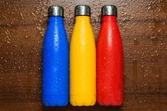 Colorful stainless thermos bottles on a wooden table sprayed with water. royalty free stock photography