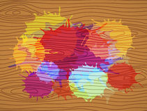Colorful stains on brown wooden plank Stock Photography
