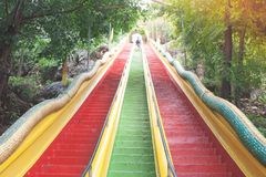 Colorful stairs going up to top floor of Thum Sua Temple or Tiger Cave Temple, Kanjanaburi Provine. Stock Photos