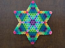 A colorful Star Of David on a wooden background. Colorful Star Of David  Magen David made out of beads on a wooden background Stock Image
